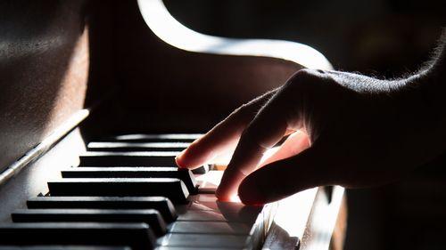 鍵盤タッチを確かめる男性の手と鍵盤